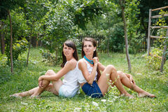 Two young females sitting on grass Stock Photo