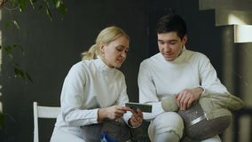 Two young fencers man and woman watching fencing tutorial on smartphone and sharing experience after training indoors. Two young fencers man and woman watching stock footage