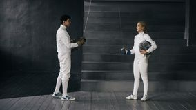 Two fencers man and woman have greeting each other and start fencing match indoors. Two young fencers men and women have greeting each other and start fencing stock photos