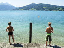 Two young fisherman. On the lake in austrian alps Stock Images
