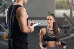 Two young fit people working in gym. royalty free stock photo