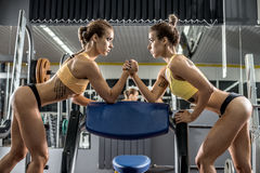 Two young fitness woman, arm wrestling in gym Royalty Free Stock Photo