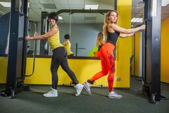 Two young fitness woman execute exercise with exercise-machine Cable Crossover in gym, horizontal photo. Royalty Free Stock Photography