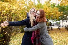 Two young friend women to get together and hug each other with a stock images