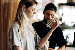 Two young friendly barista, wearing casual style,are stading next to each other and look at the glass in a cozy coffee royalty free stock image