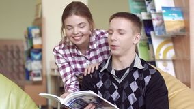 Two young friendly students looking through a book together. Two young friendly students thumbing through a book together stock video