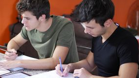 Young men busy with studies. Two young friends doing homework with tablet while sitting at table with notebooks stock footage
