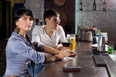 Two young friends drinking at the pub. Two young friends drinking together at the pub sitting at the bar counter with the women turning to eye the camera with a royalty free stock image