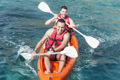 Two young friends ejoying the vacation ,going in the sea with yellow canoe Royalty Free Stock Image