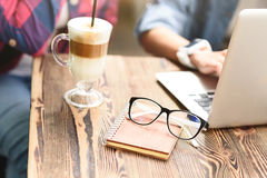 Two young friends enjoying day together. Having some coffee with my best friends. Close up of glasses lying with notepad on wooden table in coffee shop next to Stock Image