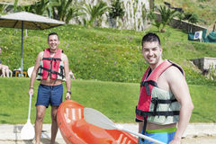 Two young friends going in the sea with canoe Royalty Free Stock Photography