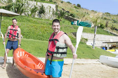 Two young friends going in the sea with orange canoe Stock Photos