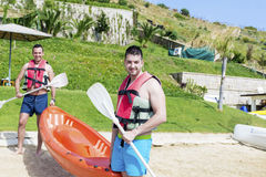 Two young friends going in the sea with orange canoe Royalty Free Stock Image