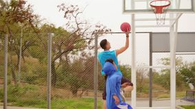 Two young friends play basketball on the street. One guy gets a ball in the basket. Slowmotion shot.  stock video footage