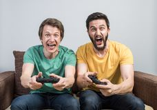 Friends playing video games. Two young friends playing awesome video games sitting on sofa and holding gamepads. Tourney or tournament concept Royalty Free Stock Photos