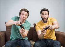 Friends playing video games. Two young friends playing awesome video games sitting on sofa and holding gamepads. Tourney or tournament concept Royalty Free Stock Images