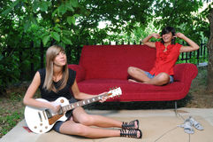 Two young friends playing the guitar Stock Photos