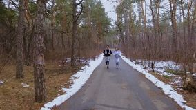 Two young friends runs along the road in winter forest. Young sport people makes morning exercises outdoors. Pretty woman and handsome man wearing sportswear stock footage