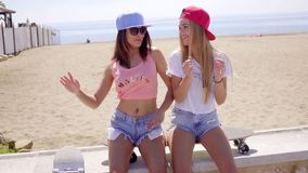 Two young friends in shorts sitting near beach stock video