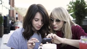 Two girlfriends web surfing from a smartphone in an outdoors cafe. Two young friends are sitting in an outside cafe and web surfing. They are discussing what stock footage