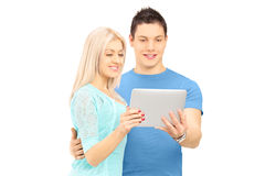 Two young friends standing close together looking at a tablet Royalty Free Stock Photos