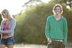 Two young friends standing in a field, one smoking Stock Images