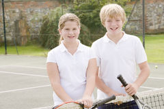 Two young friends on tennis court smiling Royalty Free Stock Images