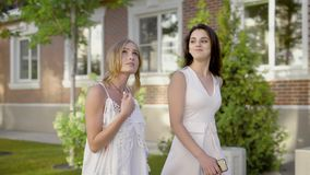 Two young friends walk next to brick country houses, women talk about life style and fashion on a summer day. Two young and attractive girlfriends stroll along stock video