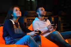 Two young gamer sitting on poufs and playing video games togethe Royalty Free Stock Images