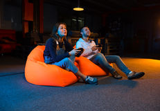 Two young gamer sitting on poufs and playing video games togethe. Playing video games while sitting on sofa Royalty Free Stock Photos