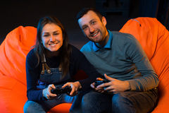 Two young gamer sitting on poufs and playing video games togethe. Playing video games while sitting on sofa Royalty Free Stock Images
