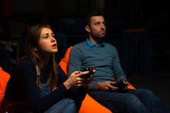 Two young gamer sitting on poufs and playing video games togethe. Playing video games while sitting on sofa Stock Images