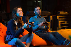 Two young gamer sitting on poufs and playing video games togethe. Playing video games while sitting on sofa Stock Photo