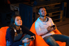 Two young gamer sitting on poufs and playing video games togethe Royalty Free Stock Photo