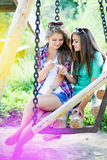 Two young girl friends looking on mobile phone Stock Images