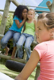 Two young girl friends at a playground whispering