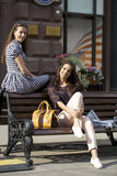 Two young girl friends sitting on bench in the town center Royalty Free Stock Photo