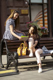 Two young girl friends sitting on bench in the town center Stock Photos