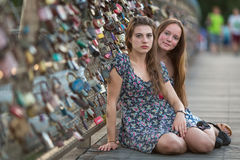 Two young girl friends sitting on a bridge with love locks. Happy. Royalty Free Stock Images