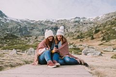 Two young girl friends sitting in the meadow look at something on the phone royalty free stock images