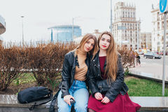 Two young girl friends sitting together and having fun Outdoors. lifestyle. Two young girl friends sitting together and having fun in city .Outdoors. lifestyle Stock Photo