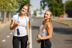 Gymnastics girls with jumping ropes on a park background. Sports friends. Active youth concept. Stock Photo