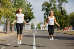 Gymnastics girls with jumping ropes on a park background. Sports friends. Active youth concept. Royalty Free Stock Photos