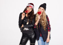 Two young girl friends standing together with red lollipop nex to white wall and having fun. Showing signs with hands. Looking at Royalty Free Stock Images