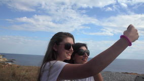 Two Young Girl Friends Taking Selfie on sea. Slowmotion stock footage
