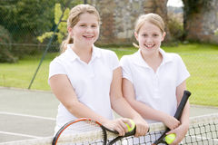 Two young girl friends on tennis court smiling Stock Photos