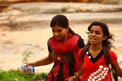 Two Young Girl Friends Walking in a Park. Two young Indian girl friends walking in  famous Lalbagh Botanical Garden holding hands Stock Image