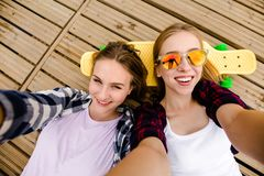 Two young girl in hipster outfit making selfie while lying with on wooden pier stock photography