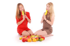 Two young girl hold a banana like a guns Royalty Free Stock Photography