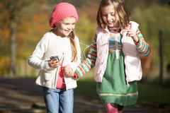 Two Young Girl Listening To MP3 Player Outdoors Stock Photo